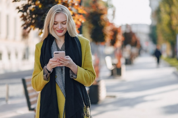 Bonita mulher loira atraente emocional no casaco com smartphone caminha pelas ruas da cidade. comunicação durante a caminhada, estilo de vida, rua.