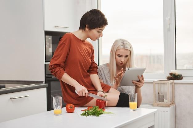 Bonita mulher loira lendo feed em tablet com a namorada enquanto ela corta legumes, preparando salada