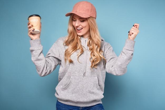 Bonita mulher loira positiva na tampa rosa com café