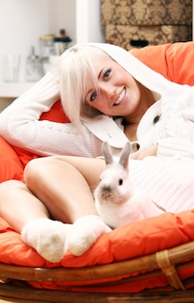 Bonita mulher loira sentada na cadeira com coelho