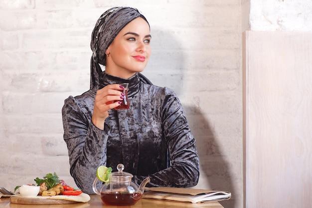 Bonita mulher muçulmana bebendo chá em um café