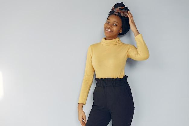 Bonita mulher negra em pé em uma parede branca