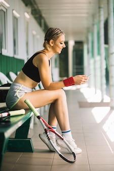 Bonita mulher olhando para o celular em uma quadra de tênis