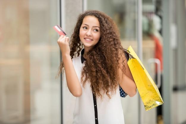 Bonita mulher segurando sacolas de compras e mostrando o cartão de crédito em branco