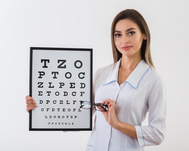 Bonita mulher segurando um painel de teste do olho