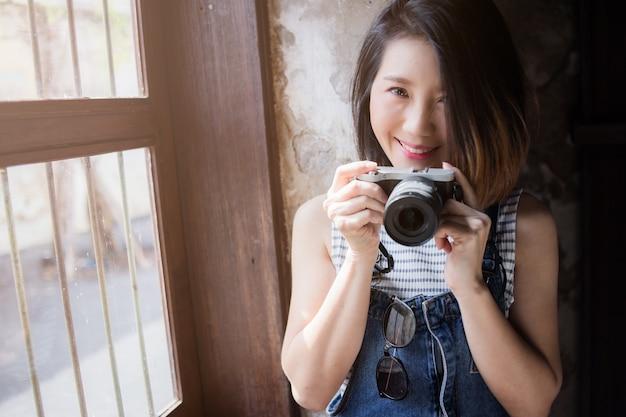 Bonita roupa casual asiática com câmera e material de viagem
