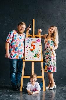 Bonita, sorridente, toda a família com um pincel nas mãos desenha um cavalete. o conceito de educação, talento, família feliz ou parentalidade.