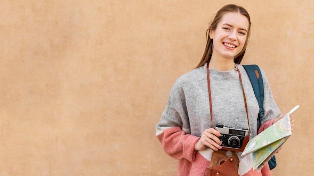 Bonita turista feminina segurando o mapa e a câmera copiam o espaço