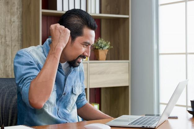 Bonitão barbudo levantou o punho expressando confiança enquanto estiver usando o laptop.