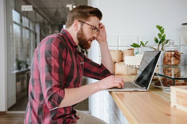 Bonitão barbudo olhando para a tela do laptop em surpresa