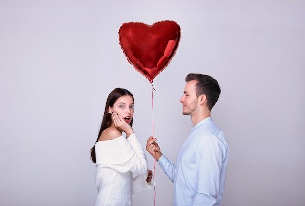 Bonitão elegante dá um balão para uma mulher.