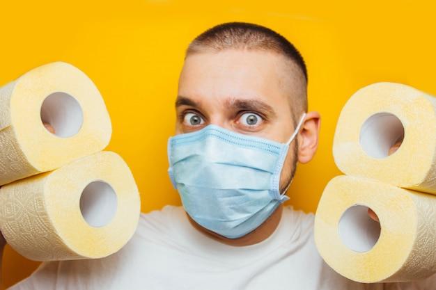 Bonitão em uma máscara protetora se esconde atrás de uma parede de papel higiênico para evitar a infecção por coronavírus. fundo amarelo conceito de flash covid-19. isolamento doméstico.