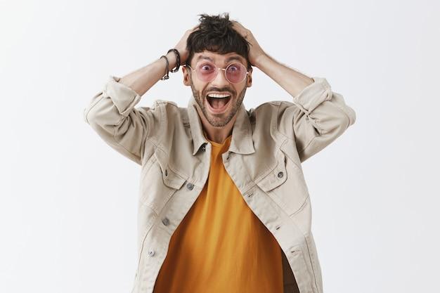 Bonitão extremamente feliz posando contra a parede branca com óculos escuros