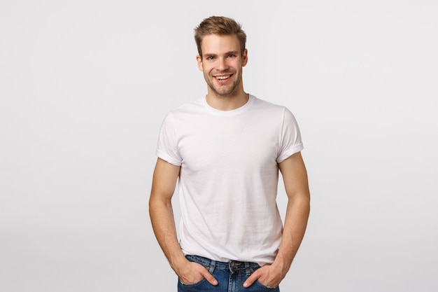 Bonitão loiro com olhos azuis e camiseta branca posando