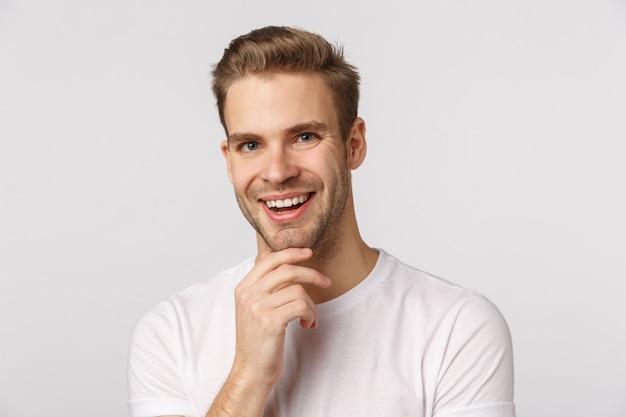Bonitão loiro com olhos azuis e camiseta branca sorrindo