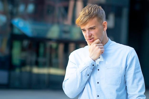Bonitão, segurando-se no queixo, vestido formalmente com uma camisa branca. dor de cabeça ou febre em um homem.