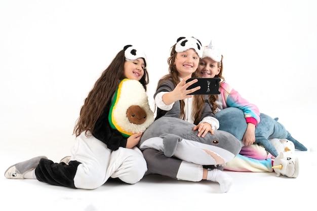 Bonitas garotas adolescentes em kigurumi e máscaras de dormir sorrindo e gravando um vídeo.