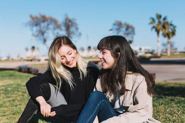 Bonitas namoradas conversando sobre grama verde