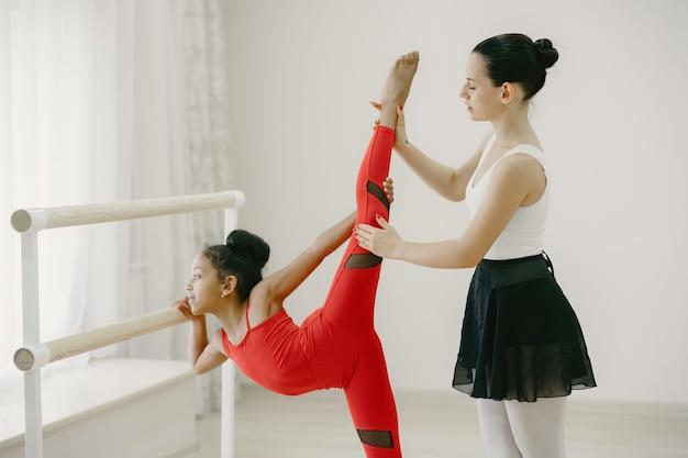 Bonitinha bailarina em traje esportivo vermelho. criança dançando na sala. garoto na aula de dança com professor