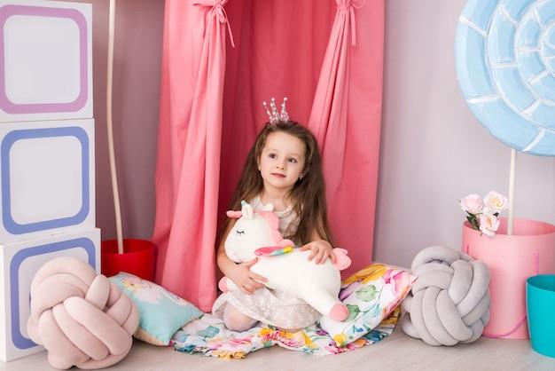 Bonitinha em um vestido inteligente no fundo de um quarto de criança linda. unicórnio de brinquedo em suas mãos.
