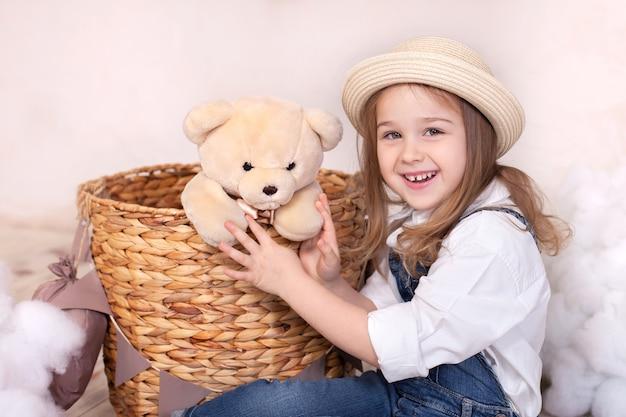 Bonitinha está jogando em casa com um ursinho de pelúcia. menina está sonhando. uma menina brinca na sala de crianças com brinquedo. closeup retrato de rosto de um bebê fofo. infância. aniversário. sorria, querida. dentes saudáveis