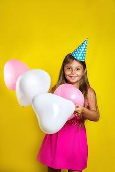 Bonitinha usando um chapéu de festa no aniversário dela. garota feliz com balões coloridos