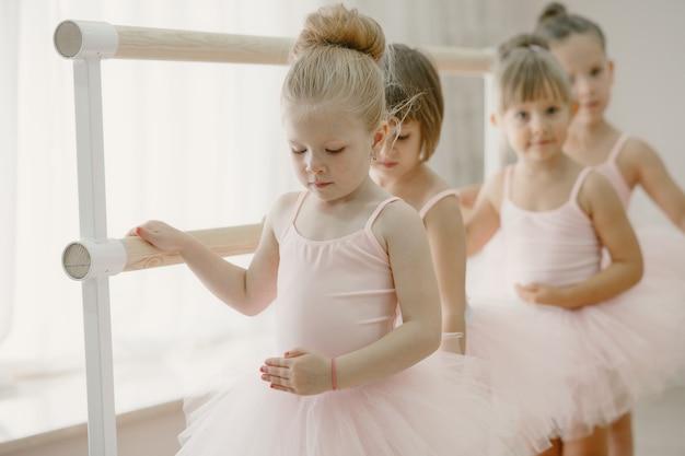 Bonitinhas bailarinas em traje de balé rosa. crianças em sapatilhas de ponta dançam na sala