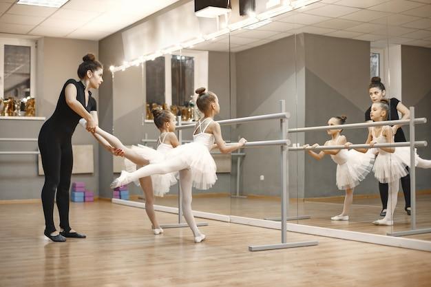 Bonitinhas bailarinas em traje de balé rosa. crianças em sapatilhas de ponta estão dançando na sala. criança na aula de dança com o professor.