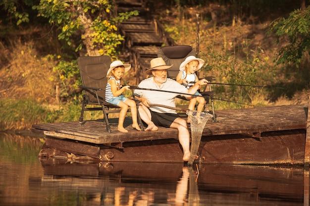Bonitinhas garotinhas e seu avô estão pescando no lago ou rio. descansando no cais perto de água e floresta na hora do sol do dia de verão. conceito de família, recreação, infância, natureza.