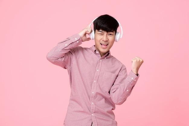 Bonitinho sorrindo homem asiático usando fones de ouvido, ouvindo música