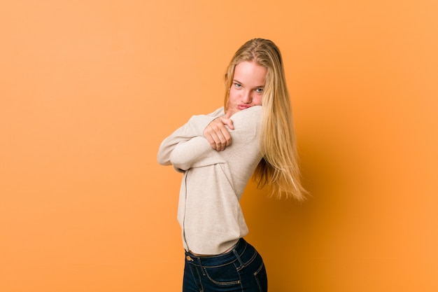 Bonito adolescente caucasiano posando em pé contra uma parede laranja
