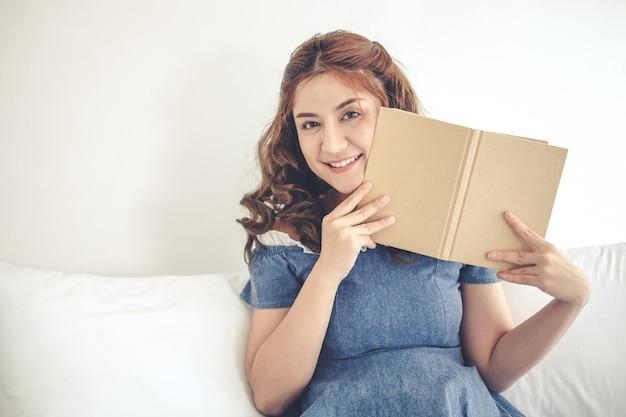 Bonito adorável jovem smilling mulher lendo livro na cama