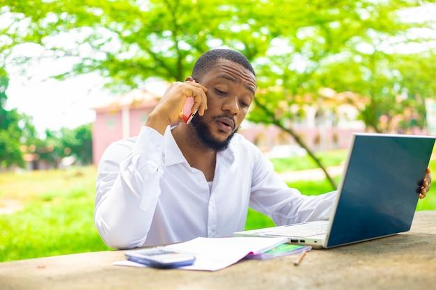 Bonito africano fazendo ligações na escola enquanto realiza seu projeto