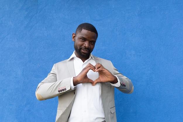 Bonito afro-americano mostra mãos com coração