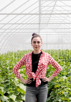 Bonito agricultor feminino em estufa