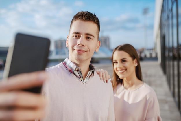 Bonito alegre casal dançando ao ar livre e tomando selfie