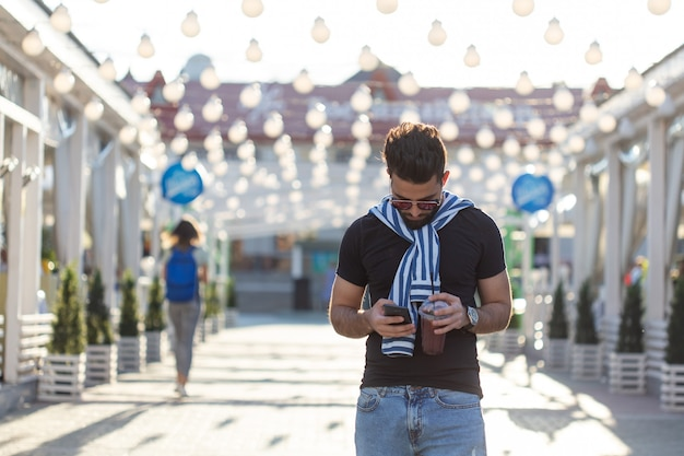 Bonito alegre jovem estudante árabe com um bigode estiloso e uma barba com suco nas mãos, andando pela cidade após um dia de trabalho. conceito de positivo e descanso.