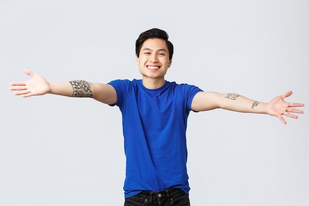 Bonito, amigável e sorridente homem asiático, estudante do sexo masculino com camiseta azul, espalhe as mãos para os lados, dando boas-vindas, cumprimentando amigos, quer abraçar ou acariciar algo, estando em um fundo cinza.