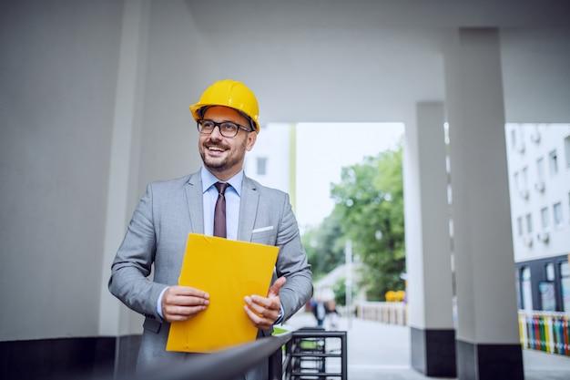 Bonito arquiteto elegante sorridente no terno e com o capacete na cabeça em pé ao ar livre com pasta nas mãos.