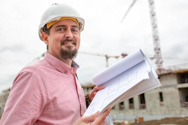 Bonito arquiteto ou supervisor em pé ao ar livre em um canteiro de obras, segurando uma planta nas mãos, olhando para a câmera com um sorriso amigável.