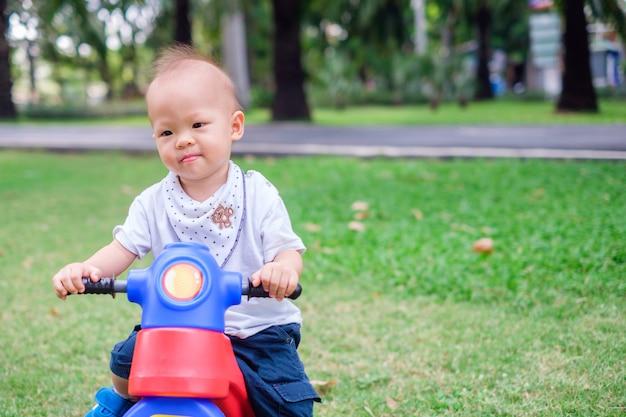 Bonito asiático 1 ano de idade criança bebê menino andando de triciclo no parque de verão