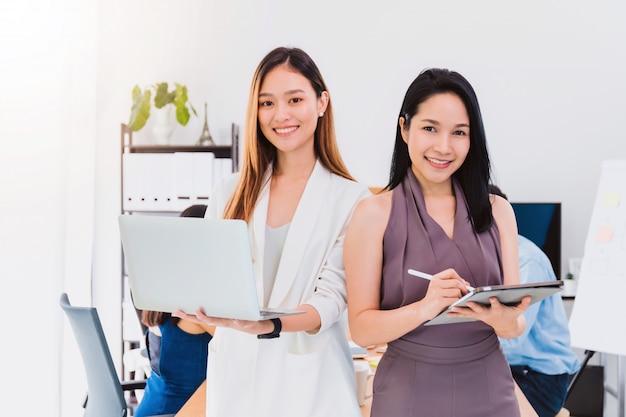 Bonito asiático autorize a mulher que guarda o portátil ee tabuleta com o amigo que trabalha na sala de reuniões no escritório. inicialização do proprietário empresária com confiante e alegre.