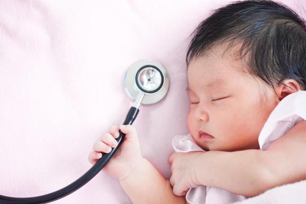 Bonito, asiático, recém nascido, bebê, menina, dormir, segurando, médico, estetoscópio, mão