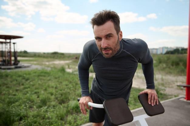 Bonito atleta masculino caucasiano, esportivo, em roupas esportivas, fazendo flexões nas barras irregulares, enquanto treinava ao ar livre em um playground de verão, olhando para a câmera