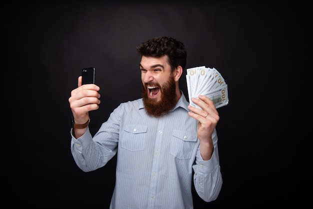 Bonito barbudo animado, gritando e comemorando o que ganhou, enquanto segura um telefone celular e muito dinheiro