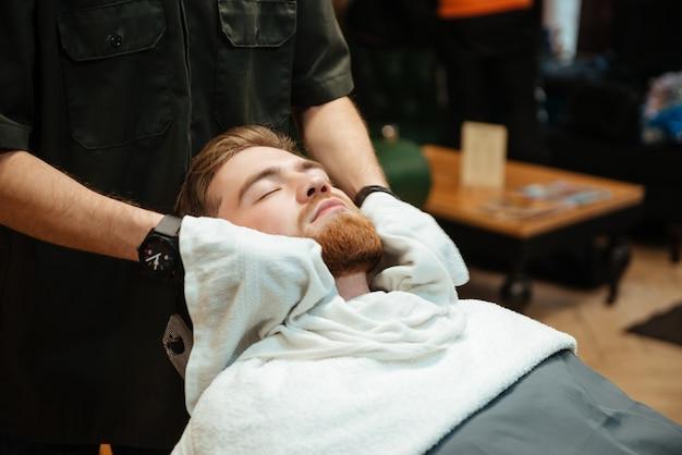 Bonito barbudo homem ficando barba raspando por cabeleireiro enquanto está na cadeira de barbearia.