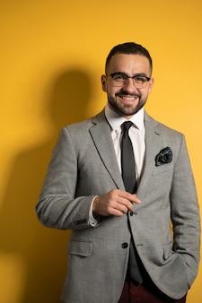 Bonito barbudo sorridente homem elegante usando óculos com roupa formal com uma mão levantada em pé isolado no fundo amarelo.