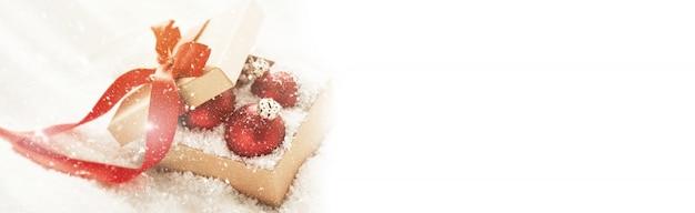Bonito baubles clássicos vermelhos ou decoração de natal em uma caixa de presente com neve, conceito de natal