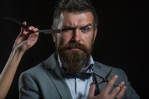 Bonito cabeleireiro barbudo uma navalha, barbearia. homem barbudo, barba comprida, brutal, machista, hipster caucasiano com bigode, corte de cabelo, com navalha de barbeiro ou cabeleireiro.