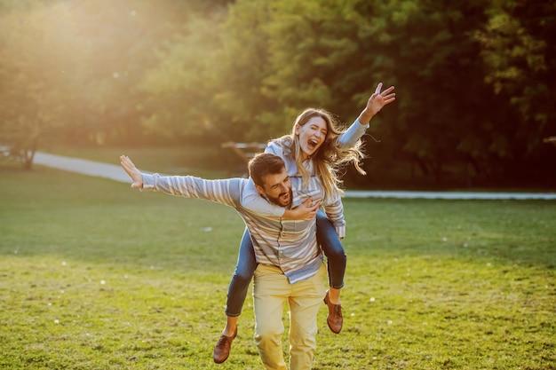 Bonito casal caucasiano apaixonado tendo nas costas e se divertindo na natureza.
